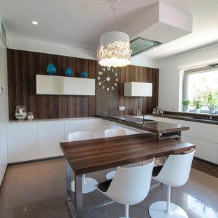 バーリの大きいコンテンポラリースタイルのおしゃれなキッチン (アンダーカウンターシンク、フラットパネル扉のキャビネット、白いキャビネット、茶色いキッチンパネル、パネルと同色の調理設備、ガラス板のキッチンパネル) の写真