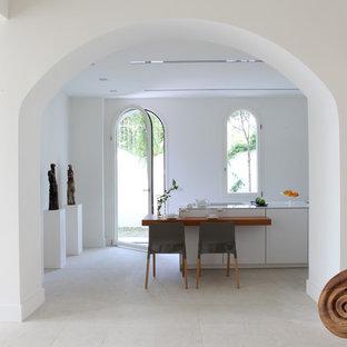 Diseño de cocina comedor mediterránea con armarios con paneles lisos, puertas de armario blancas, suelo de travertino y una isla
