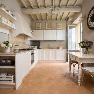 Bild på ett shabby chic-inspirerat beige beige kök, med luckor med infälld panel, vita skåp, rostfria vitvaror, klinkergolv i terrakotta och brunt golv