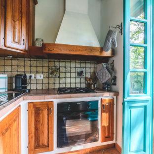 他の地域の小さいモダンスタイルのおしゃれなキッチン (ドロップインシンク、ルーバー扉のキャビネット、中間色木目調キャビネット、ライムストーンカウンター、白いキッチンパネル、モザイクタイルのキッチンパネル、黒い調理設備、ライムストーンの床、アイランドなし、オレンジの床、ピンクのキッチンカウンター) の写真
