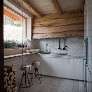 Immagine di una piccola cucina lineare rustica chiusa con lavello a vasca singola, ante lisce, ante bianche, paraspruzzi multicolore, elettrodomestici da incasso, parquet chiaro, nessuna isola e pavimento beige