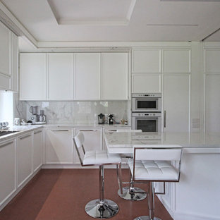 This is an example of an expansive traditional eat-in kitchen in Milan with recessed-panel cabinets, marble benchtops, white appliances, ceramic floors, with island, red floor and white benchtop.