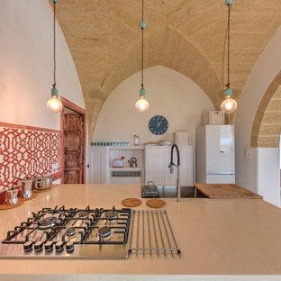 Foto di una cucina mediterranea con top beige, lavello da incasso, ante con riquadro incassato, ante bianche, paraspruzzi rosso, elettrodomestici bianchi, una penisola e pavimento bianco