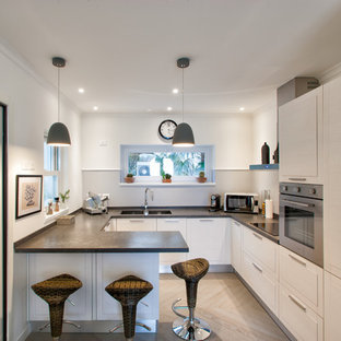 Design ideas for a mid-sized contemporary u-shaped kitchen in Other with an integrated sink, raised-panel cabinets, white cabinets, white splashback, stainless steel appliances, light hardwood floors and a peninsula.