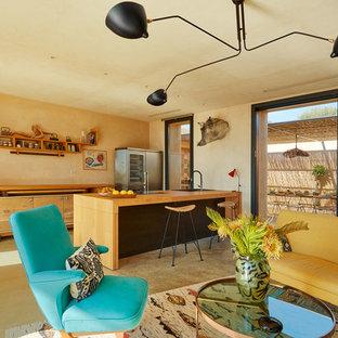Esempio di una cucina tropicale con lavello da incasso, ante lisce, ante in legno chiaro, top in legno, paraspruzzi beige, elettrodomestici in acciaio inossidabile, pavimento in cemento, una penisola, pavimento beige e top beige