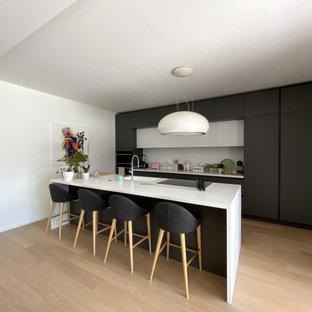 Ispirazione per una grande cucina contemporanea con lavello integrato, ante lisce, ante nere, top in superficie solida, paraspruzzi bianco, elettrodomestici neri, parquet chiaro e top bianco