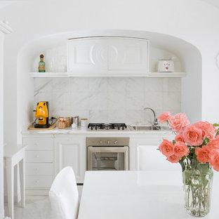 ナポリの小さい地中海スタイルのおしゃれなキッチン (ドロップインシンク、白いキャビネット、大理石カウンター、白いキッチンパネル、石スラブのキッチンパネル、シルバーの調理設備の) の写真