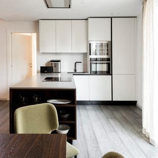 Idee per una cucina minimal di medie dimensioni con lavello sottopiano, ante lisce, ante bianche, elettrodomestici da incasso, penisola, pavimento grigio e top grigio