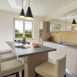 Offene, Zweizeilige Moderne Küche mit Kücheninsel, hellen Holzschränken, Rückwand aus Backstein, Porzellan-Bodenfliesen, grauem Boden, Einbauwaschbecken, flächenbündigen Schrankfronten, Küchenrückwand in Gelb, Küchengeräten aus Edelstahl und grauer Arbeitsplatte in Sonstige