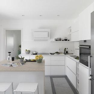 Immagine di una cucina minimal di medie dimensioni con lavello a doppia vasca, ante lisce, ante bianche, top in superficie solida, paraspruzzi bianco, elettrodomestici in acciaio inossidabile e isola