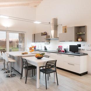 Foto di una cucina contemporanea con lavello sottopiano, ante lisce, ante bianche, parquet chiaro, pavimento beige, top grigio e soffitto a volta