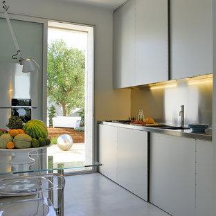 Esempio di una cucina design di medie dimensioni con top in acciaio inossidabile, pavimento in cemento, lavello integrato, ante lisce, ante bianche, paraspruzzi a effetto metallico, paraspruzzi con piastrelle di metallo e elettrodomestici in acciaio inossidabile