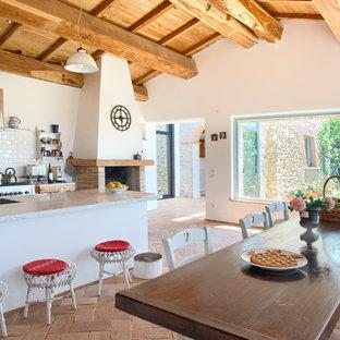 Aménagement d'une cuisine américaine méditerranéenne avec une crédence blanche, une crédence en carrelage métro, un électroménager en acier inoxydable, un sol orange, un plan de travail gris et un plafond en bois.