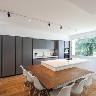 Immagine di una cucina design con lavello sottopiano, ante lisce, ante grigie, paraspruzzi bianco, elettrodomestici neri, parquet chiaro, isola e top bianco