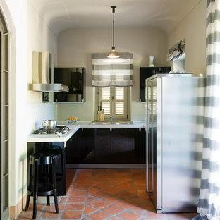 トゥーリンのモダンスタイルのおしゃれなキッチン (ドロップインシンク、大理石カウンター、シルバーの調理設備の、テラコッタタイルの床、赤い床) の写真