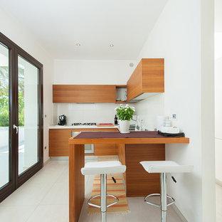 Foto di una piccola cucina minimal con ante lisce, paraspruzzi bianco, penisola, lavello a doppia vasca, ante in legno chiaro, elettrodomestici in acciaio inossidabile e pavimento bianco