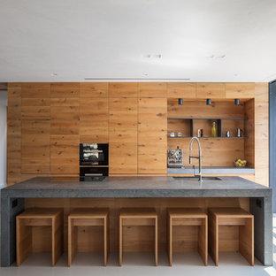 Idee per una cucina lineare minimal con ante in legno scuro, un'isola e top grigio