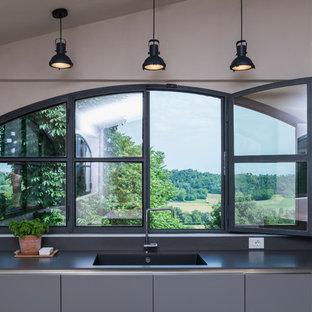 Immagine di una cucina country di medie dimensioni con lavello integrato, ante grigie, top in superficie solida, paraspruzzi grigio, isola, top grigio e ante lisce