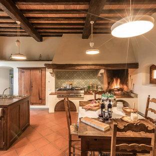 Неиссякаемый источник вдохновения для домашнего уюта: большая линейная кухня в стиле кантри с обеденным столом, тройной раковиной, фасадами с утопленной филенкой, темными деревянными фасадами, разноцветным фартуком, фартуком из керамической плитки, техникой из нержавеющей стали, полом из терракотовой плитки, островом и красным полом