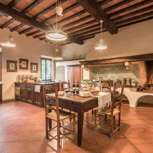 フィレンツェの大きいカントリー風おしゃれなキッチン (トリプルシンク、落し込みパネル扉のキャビネット、濃色木目調キャビネット、マルチカラーのキッチンパネル、セラミックタイルのキッチンパネル、シルバーの調理設備の、テラコッタタイルの床、赤い床) の写真