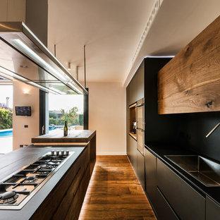 Cette image montre une cuisine ouverte design avec un évier posé, des portes de placard en bois brun, un plan de travail en surface solide, une crédence noire, une crédence en ardoise, un sol en bois brun et un îlot central.