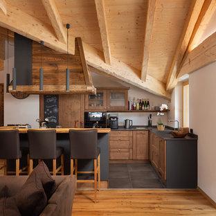Idee per una cucina a L rustica con ante in legno scuro, isola, top nero, ante in stile shaker e pavimento grigio