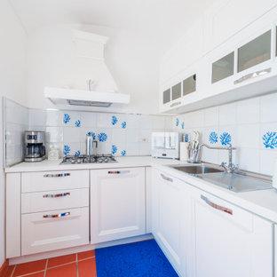 Esempio di una piccola cucina a L mediterranea con lavello da incasso, ante con riquadro incassato, ante bianche, top in laminato, paraspruzzi bianco, paraspruzzi in gres porcellanato, elettrodomestici bianchi, pavimento in terracotta, isola, pavimento marrone, top bianco e soffitto a volta