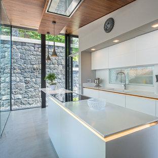 Esempio di una cucina lineare design di medie dimensioni con lavello integrato, ante di vetro, ante bianche, paraspruzzi con lastra di vetro, pavimento in gres porcellanato e un'isola