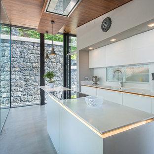 Esempio di una cucina moderna con lavello integrato, ante lisce, ante bianche, paraspruzzi bianco, pavimento in cemento, isola e pavimento grigio