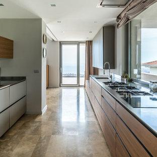 Immagine di una cucina parallela design con lavello integrato, ante lisce, ante grigie, top in acciaio inossidabile, paraspruzzi a finestra, nessuna isola e pavimento beige