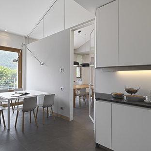 トゥーリンの大きいコンテンポラリースタイルのおしゃれなキッチン (ドロップインシンク、フラットパネル扉のキャビネット、白いキャビネット、大理石カウンター、白いキッチンパネル、ガラス板のキッチンパネル、シルバーの調理設備の、アイランドなし、セラミックタイルの床、グレーの床) の写真