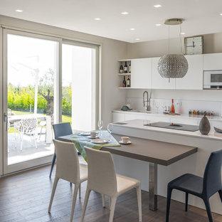 Foto di una cucina lineare stile marinaro di medie dimensioni con lavello sottopiano, paraspruzzi bianco, parquet scuro, isola, pavimento multicolore, top bianco e soffitto ribassato