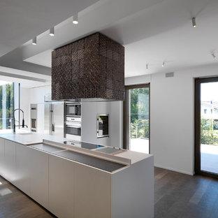 Foto di una cucina minimalista con ante lisce, ante bianche, lavello integrato, elettrodomestici in acciaio inossidabile, pavimento in legno massello medio, pavimento marrone e top bianco