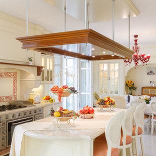 Ispirazione per una cucina abitabile classica con ante con bugna sagomata, ante beige, paraspruzzi multicolore, elettrodomestici in acciaio inossidabile, isola, pavimento beige e top beige