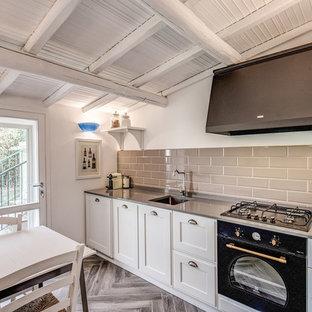 他の地域の小さい地中海スタイルのおしゃれなキッチン (アンダーカウンターシンク、レイズドパネル扉のキャビネット、白いキャビネット、グレーのキッチンパネル、サブウェイタイルのキッチンパネル、黒い調理設備、アイランドなし) の写真