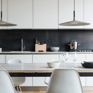 Photo of a modern single-wall eat-in kitchen in Rome with an integrated sink, flat-panel cabinets, white cabinets, quartzite benchtops, black splashback, slate splashback, white appliances, light hardwood floors and white benchtop.