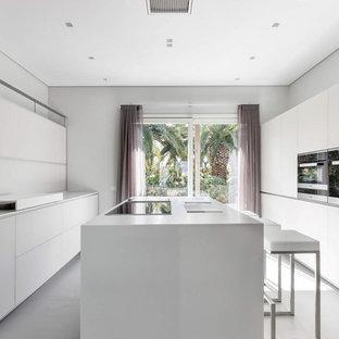 Ispirazione per un grande cucina con isola centrale contemporaneo con ante bianche, paraspruzzi bianco, pavimento bianco, top bianco, ante lisce e elettrodomestici neri