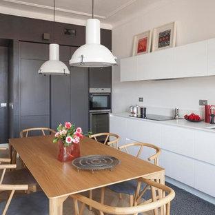 Immagine di una cucina design con lavello a doppia vasca, ante lisce, ante bianche, paraspruzzi bianco, elettrodomestici in acciaio inossidabile, pavimento in legno massello medio, pavimento marrone e top bianco