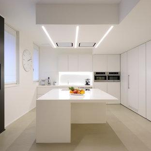 Idee per una cucina a L minimalista chiusa e di medie dimensioni con lavello a doppia vasca, ante lisce, paraspruzzi bianco, elettrodomestici in acciaio inossidabile, isola e pavimento beige