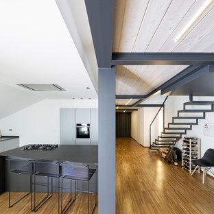 Ispirazione per una cucina design con ante lisce, ante grigie, elettrodomestici neri, pavimento in bambù, isola e top grigio