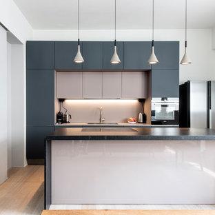Inredning av ett modernt stort svart svart kök, med släta luckor, svarta vitvaror, ljust trägolv, en köksö, en nedsänkt diskho, grå skåp, marmorbänkskiva, rosa stänkskydd, glaspanel som stänkskydd och beiget golv