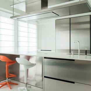 Foto di una cucina parallela minimal con lavello sottopiano, ante in acciaio inossidabile, penisola, top bianco, ante lisce, paraspruzzi bianco, elettrodomestici in acciaio inossidabile e pavimento bianco