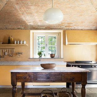 Foto på ett medelhavsstil kök, med släta luckor, gula skåp, svarta vitvaror, en köksö, marmorbänkskiva och gult stänkskydd