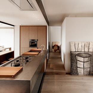 Ispirazione per un'ampia cucina minimal con ante lisce, ante in legno scuro, pavimento in legno massello medio e isola