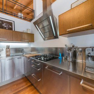 Esempio di una cucina industriale con lavello da incasso, ante lisce, ante in acciaio inossidabile, top in acciaio inossidabile e paraspruzzi a effetto metallico