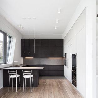 Esempio di una cucina ad U minimalista con ante lisce, ante nere, paraspruzzi grigio, penisola, pavimento in legno massello medio, pavimento marrone e top grigio