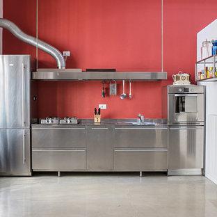На фото: большая прямая кухня в стиле лофт с плоскими фасадами, фасадами из нержавеющей стали, столешницей из нержавеющей стали, красным фартуком и техникой из нержавеющей стали с