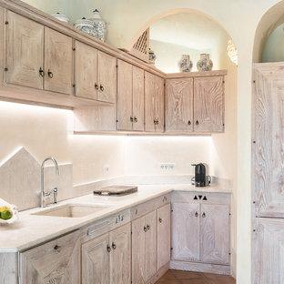 他の地域の地中海スタイルのおしゃれなL型キッチン (淡色木目調キャビネット、ベージュキッチンパネル、アンダーカウンターシンク、落し込みパネル扉のキャビネット、石スラブのキッチンパネル、テラコッタタイルの床、アイランドなし、茶色い床、ベージュのキッチンカウンター) の写真