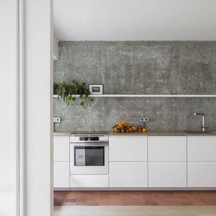 Ejemplo de cocina lineal, actual, pequeña, con armarios con paneles lisos, puertas de armario blancas, salpicadero verde, electrodomésticos de acero inoxidable, suelo de baldosas de terracota, suelo rojo y encimeras marrones