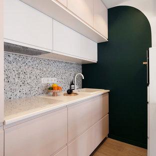 На фото: маленькая прямая кухня-гостиная в стиле модернизм с одинарной раковиной, фасадами с декоративным кантом, розовыми фасадами, столешницей из ламината, разноцветным фартуком, фартуком из керамической плитки, белой техникой, полом из винила, бежевым полом и белой столешницей
